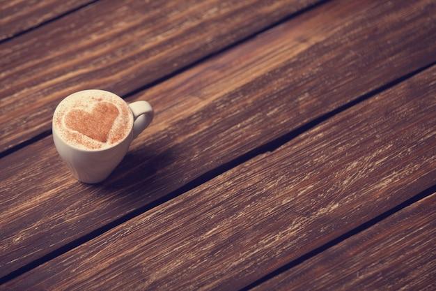 Tasse de café avec coeur forme sur table en bois.