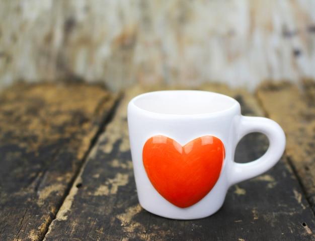 Tasse à café coeur orange sur la table en bois