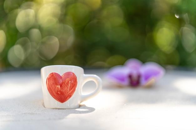 Tasse de café avec coeur rouge imprimé sur du sable sur fond de fleur flou.