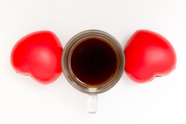 Tasse de café avec des coeurs sur la table blanche.