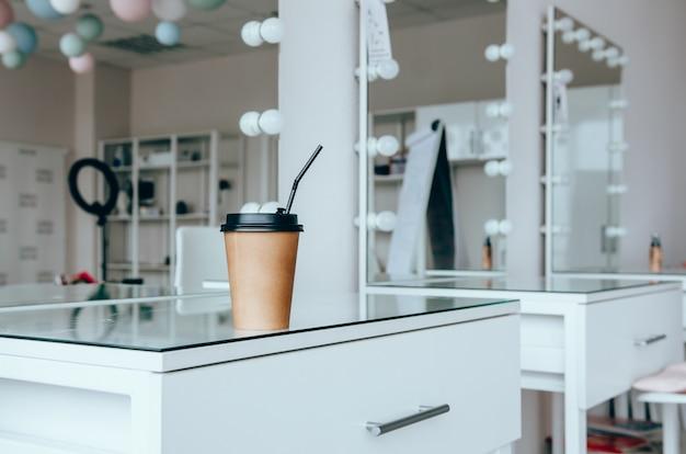Une tasse de café sur la coiffeuse près du miroir dans la salle de maquillage