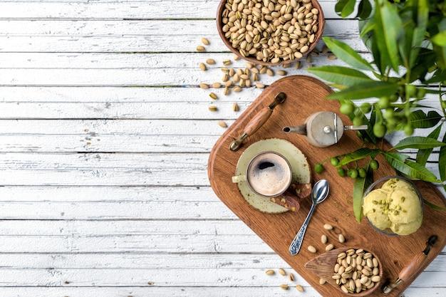 Tasse à café, collations et dessert sur fond de bois blanc
