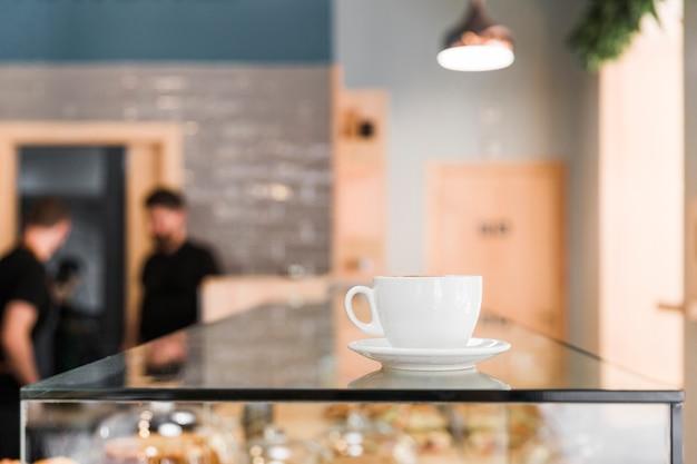 Tasse à café sur un comptoir en verre dans un café