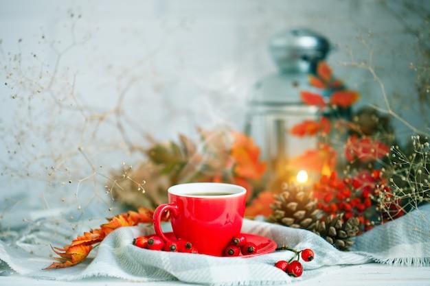 Tasse de café, des cônes et des feuilles d'automne sur une table en bois.
