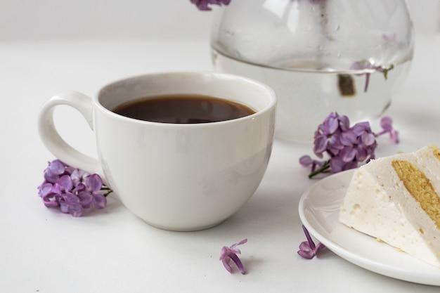 Tasse de café et cornes de gâteau de nature morte avec un bouquet de lilas sur une table blanche, une tasse de café, une assiette avec un morceau de gâteau. journée internationale de la femme, le 8 mars