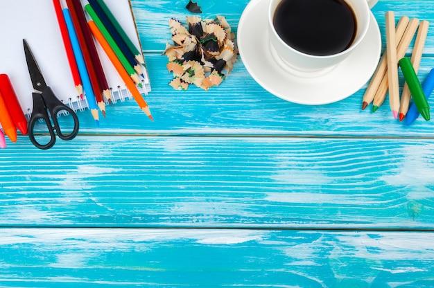 Tasse à café avec des crayons et des coupes au crayon sur fond de bois