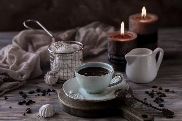 Tasse de café crema avec biscuits aux pépites de chocolat, guimauves et bougies allumées.