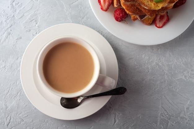 Une tasse de café avec de la crème et du pain grillé avec de la cannelle et des fraises le petit-déjeuner