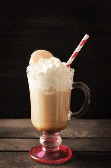 Tasse de café avec crème fouettée et macaron sur surface noire