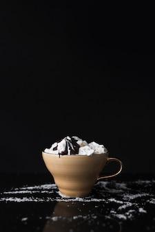 Tasse à café avec crème fouettée et sirop au chocolat sur fond noir