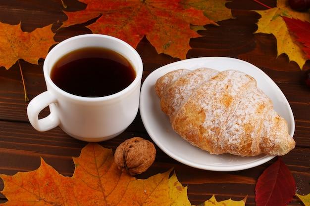 Tasse de café et croissant nature morte d'automne