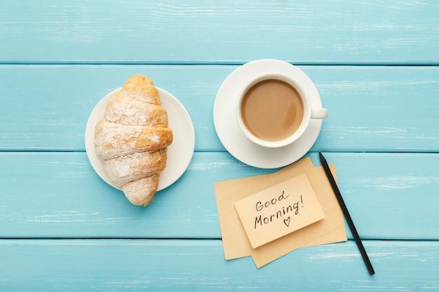 Tasse à café avec croissant et note bonjour sur une table rustique bleue d'en haut. vue de dessus sur un petit-déjeuner confortable et savoureux, espace de copie