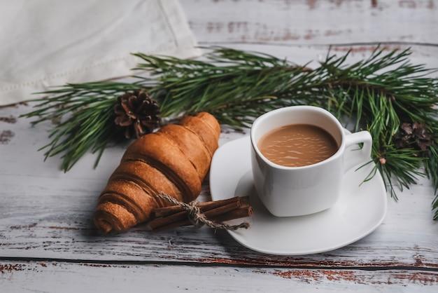 Tasse de café et un croissant pour le petit déjeuner de noël, décoré de branches de sapin et de pommes de pin