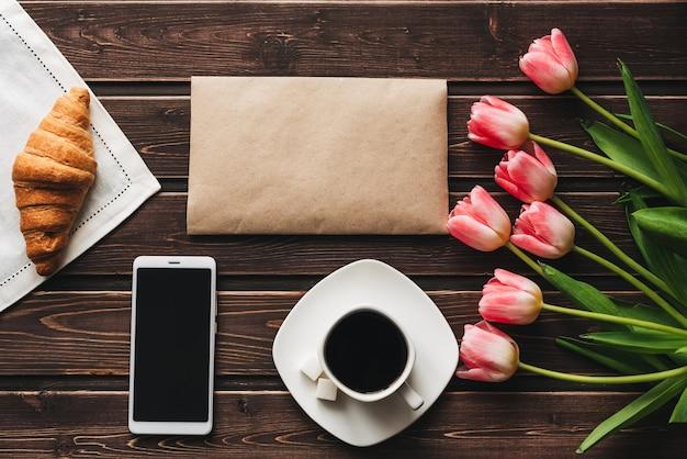 Tasse de café avec un croissant pour le petit déjeuner sur la table décorée d'un bouquet de tulipes roses et d'un smartphone