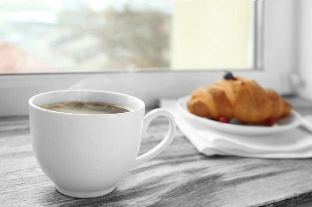 Tasse de café et croissant sur le rebord de la fenêtre