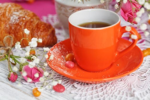 Une tasse de café et un croissant sont décorés de serviettes, de roses et de bonbons sur une table en bois blanc.
