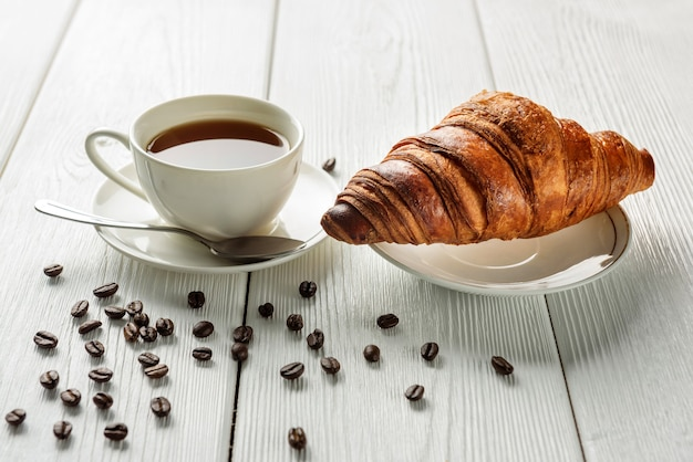 Une tasse de café et un croissant sur une table avec des grains de café saupoudrés. café et croissant en gros plan. concept de petit-déjeuner léger.