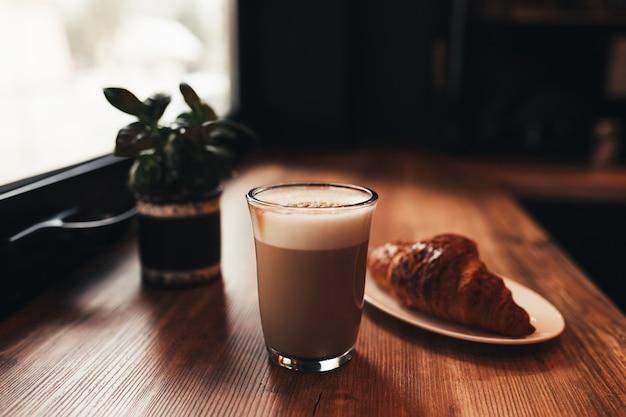 Tasse de café, croissant à table près de la fenêtre au café