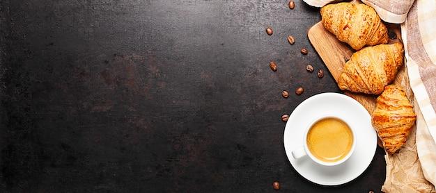 Tasse de café et croissants debout sur une planche de bois placée sur le vieux fond rustique