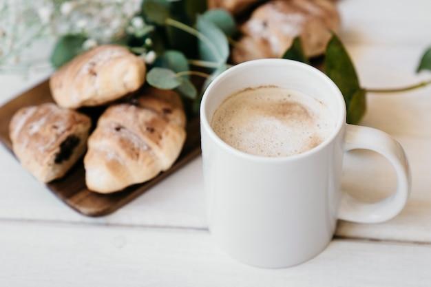 Tasse à café avec des croissants et des fleurs floues