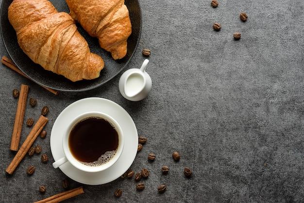 Tasse de café et croissants sur la table avec des bâtons de cannelle et des grains de café. petit déjeuner léger.