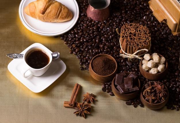 Tasse à café, cruissant, grains de café, cannelle, chocolat et sucre en cubes sur une table