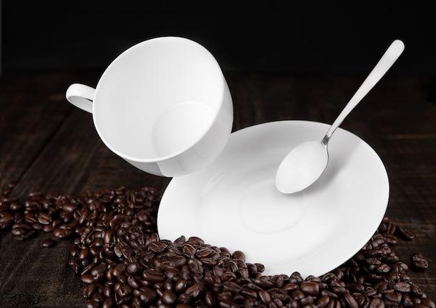 Tasse à café avec cuillère en l'air sur les haricots sur planche de bois