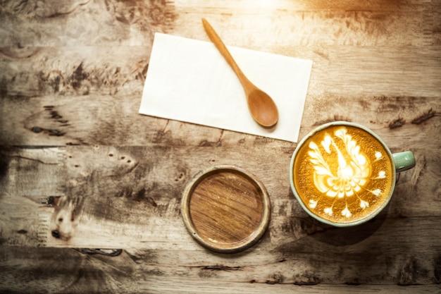 Tasse à café et cuillère latte sur table en bois dans café avec espace de copie gratuit.