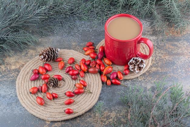 Une tasse de café avec des cynorrhodons et des pommes de pin sur fond de marbre . photo de haute qualité