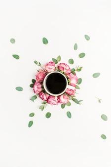 Tasse de café dans le cadre de boutons de fleurs rose rose et de branches d'eucalyptus sur blanc