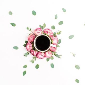 Tasse de café dans un cadre de boutons de fleurs roses roses et de branches d'eucalyptus sur fond blanc. mise à plat, vue de dessus