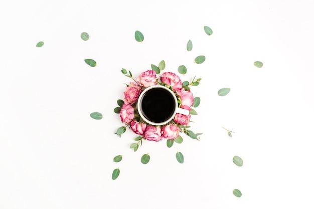 Tasse de café dans un cadre de boutons de fleurs roses roses et de branches d'eucalyptus. mise à plat, vue de dessus