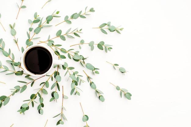 Tasse de café dans le cadre d'une branche d'eucalyptus. mise à plat, vue de dessus