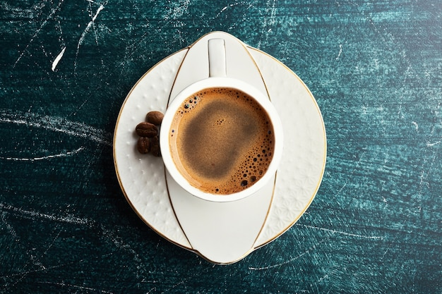Une tasse de café avec dans une soucoupe blanche.