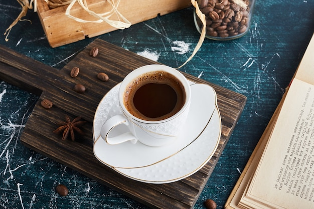 Une tasse de café dans une soucoupe blanche.