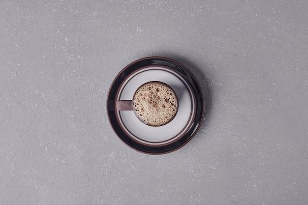 Une tasse de café dans une soucoupe décorative, vue du dessus.