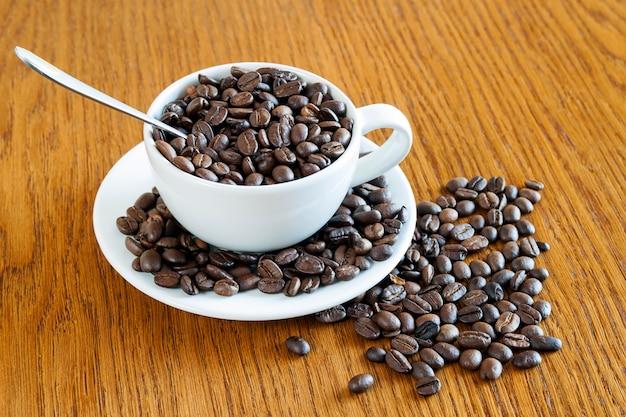Tasse de café dans une tasse blanche et grains de café sur fond de table en bois