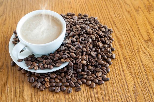 Tasse de café dans une tasse blanche et grains de café sur une table en bois.