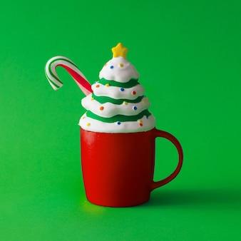 Tasse de café avec décoration d'arbre de noël avec des bonbons. boisson chaude d'hiver. concept alimentaire minimal.