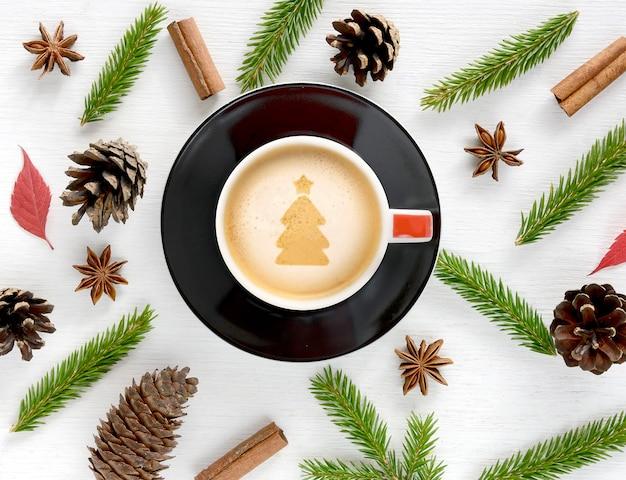 Tasse à café avec des décorations de noël sur fond de bois blanc mise à plat