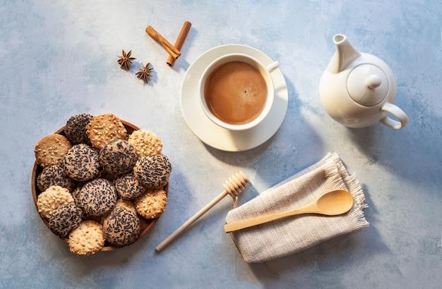 Tasse de café avec du lait et des biscuits sur fond bleu, vue haute