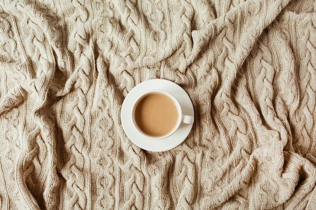 Tasse de café avec du lait sur une couverture à carreaux tricotée beige