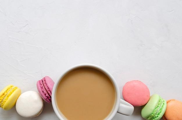 Une tasse de café avec du lait et des macarons