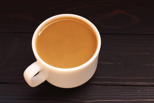 Tasse de café avec du lait sur une surface sombre