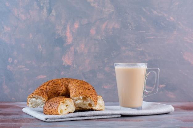 Une tasse de café avec du lait et des tranches de bagel turc se bouchent, sur le fond de marbre.
