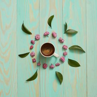 Tasse de café du matin et une belle fleurs et feuilles, vue de dessus. petit déjeuner confortable. style plat.
