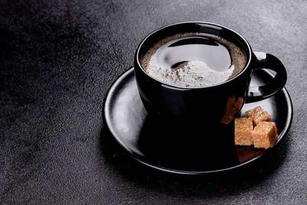 Une tasse de café du matin fraîchement parfumé pour bien démarrer la journée. belle tasse de café avec du café sur une table sombre