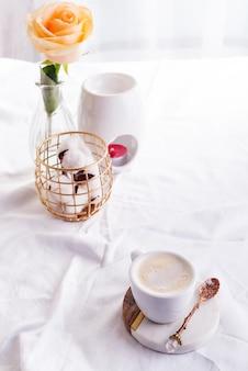 Tasse de café du matin avec des lunettes sur un cahier, une bougie et une rose sur un lit blanc