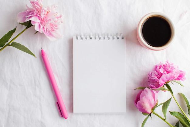 Une tasse de café du matin pour le petit déjeuner, un bloc-notes vide pour votre texte ou votre design, des fleurs de pivoine rose sur une nappe blanche