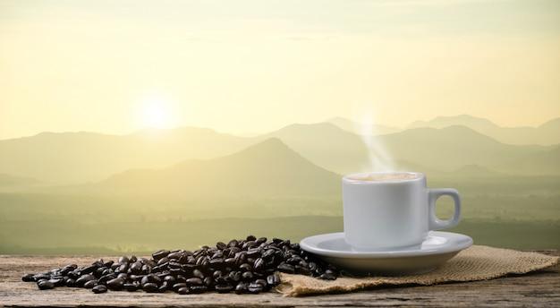 Tasse de café du matin et vue sur les grains de café torréfiés avec le soleil des montagnes